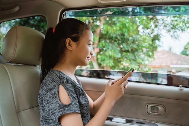 Девушка улыбается, держа телефон, сидя в машине с открытым окном во время путешествия