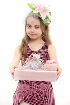 긴 금발 머리에 꽃과 소녀 미소입니다. 아이 잡고 선물 상자 흰색 절연입니다. 생일, 기념일 축하. 휴일 선물과 놀람. 박싱 데이 개념입니다.