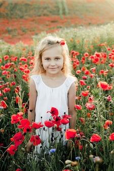A girl smiles among poppy flowers