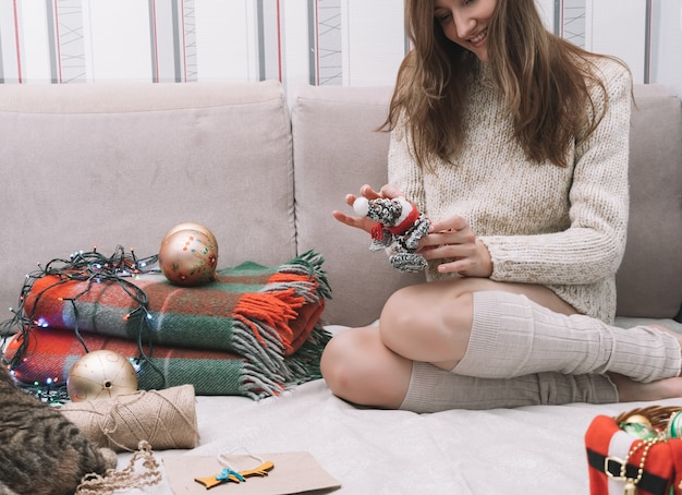 Девушка улыбается и держит в руках елочную игрушку, вокруг рождественские украшения