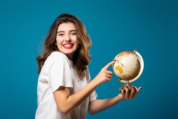 女の子は笑顔で地球を指しています
