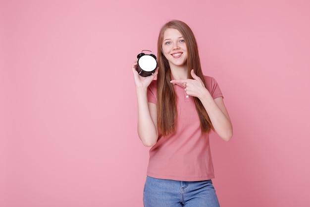 Девушка улыбается и показывает будильник на розовом фоне