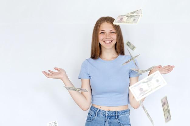 女の子は笑顔で白い背景にお金を投げる