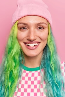 Girl smiles broadly shows white teeth has long dyed colored hair happy to meet friend wears hat isolated on pink