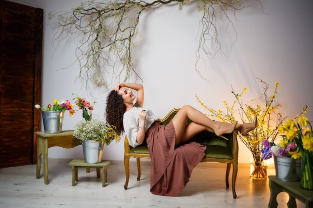 The girl smiles in a brown skirt sits on the couch. around are fresh flowers in a vase.