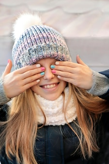 The girl smiles happily, covering her eyes with her hands with a beautiful manicure.