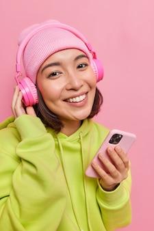 소녀 미소는 하얀 치아가 휴대폰을 들고 있는 것을 즐겁게 보여주며 분홍색에 모자와 운동복을 입은 새로운 스테레오 헤드폰을 사용합니다