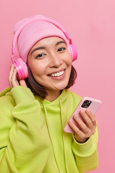 Girl smiles pleasantly shows white teeth holds mobile phone uses new stereo headphones wears hat and sweatshirt on pink