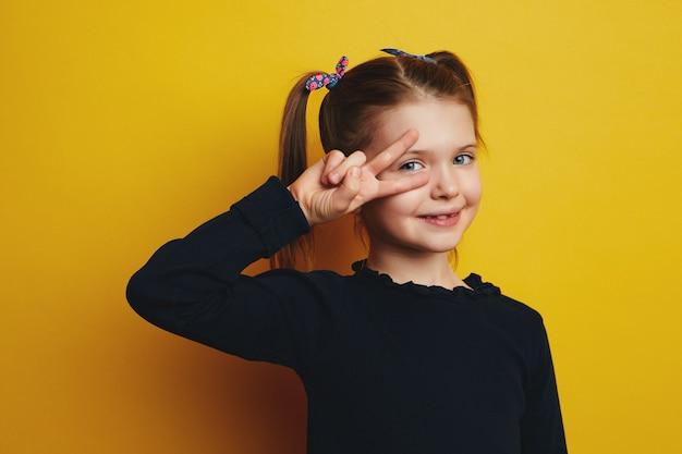 Девушка зубасто улыбается, делает жест мира поверх глаз у желтой стены