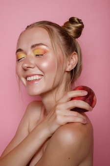 The girl smiles with bright makeup and peach on a pink wall. bright summer photo