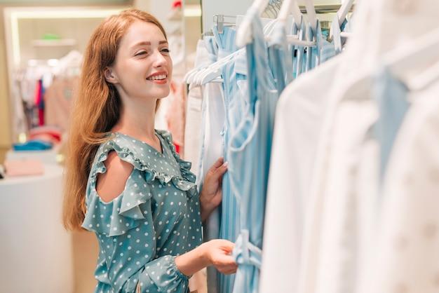 Девушка улыбается и проверяет одежду