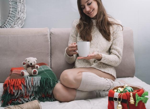 Девушка улыбается и держит чашку чая в руках, рождественские украшения вокруг