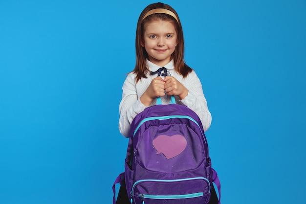 Девушка улыбается и держит рюкзак в школьной форме