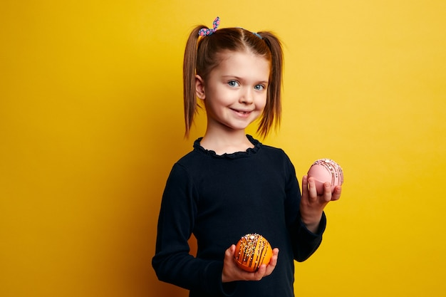 Девушка улыбается и держит в руках шоколадную бомбу, которая тает с горячим молоком
