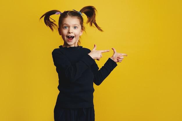 Девушка улыбается и показывает вправо обеими руками во время прыжка