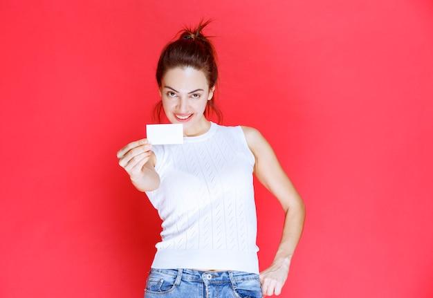 Девушка улыбается и представляет свою визитную карточку.