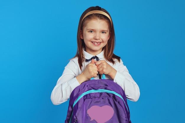 Девушка широко улыбается и держит рюкзак в школьной форме