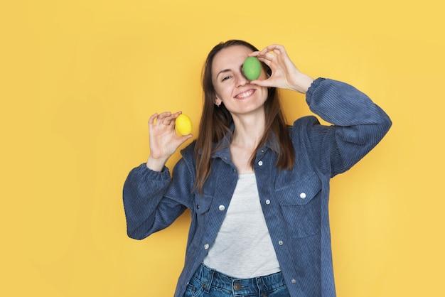 笑顔の女の子は、黄色の背景に分離された青いシャツを着たエステルの卵で目を閉じます。