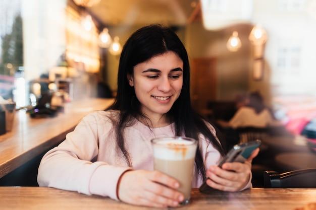 笑顔の女の子、カフェでコーヒーを飲み、電話を読んでいます。背景がぼやけている。高品質の写真