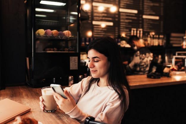 여자가 웃 고, 카페에서 커피를 마시고 전화를 읽고. 흐린 배경