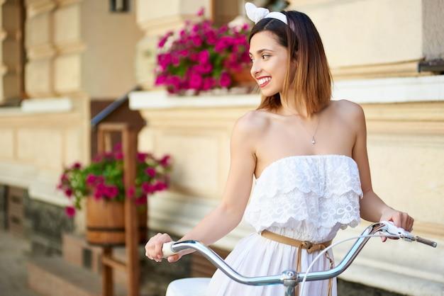 Девушка улыбается, глядя в сторону во время езды на велосипеде по улице с красивыми украшенными домами