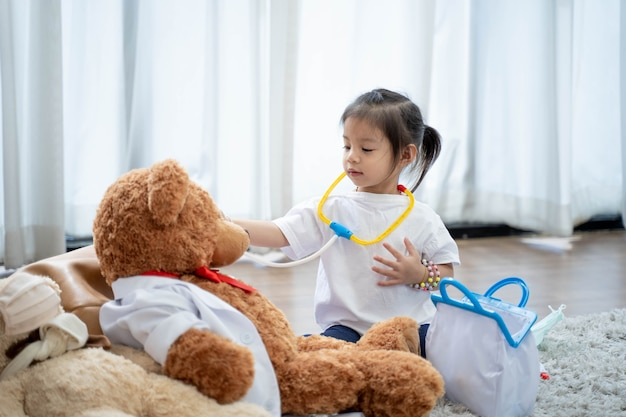 Girl smiling and lying on the floor with playing teddy bear