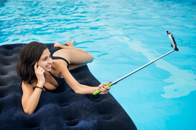 Girl smiling and makes selfie photo on the phone with selfie stick on a mattress in the pool at the resort