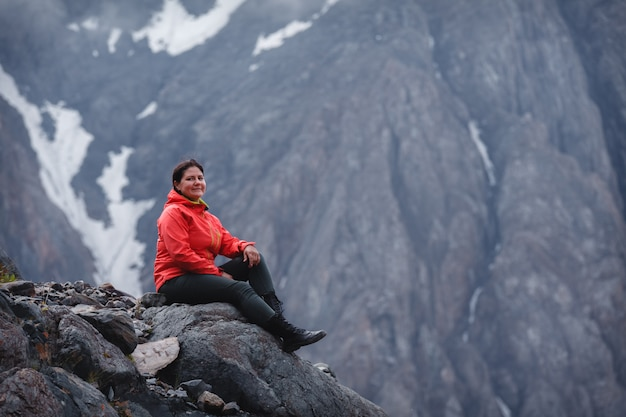 Girl smiling in a red jacket sitting on the mountain.