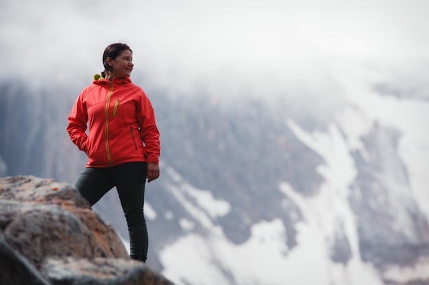 Girl smiling in a red jacket, standing on the mountain.