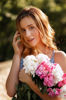 Girl smiling. romantic image for walking in the city. in her hands are flowers.