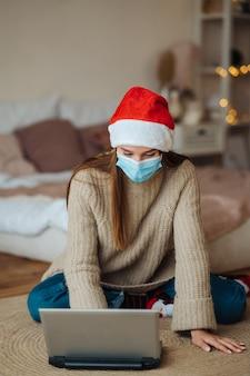 집에서 크리스마스 축하 기간 동안 노트북에 온라인 친구와 이야기하는 동안 웃는 소녀. 코로나 바이러스 제한에 따라 새해와 크리스마스를 축하하는 개념. 방역 휴가
