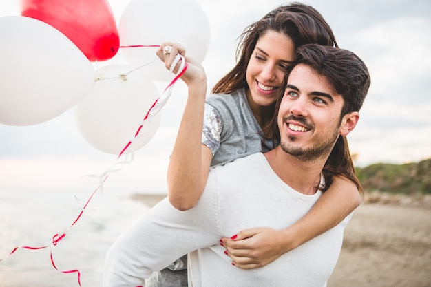 Girl smiling with balloons while her boyfriend carries her on her back