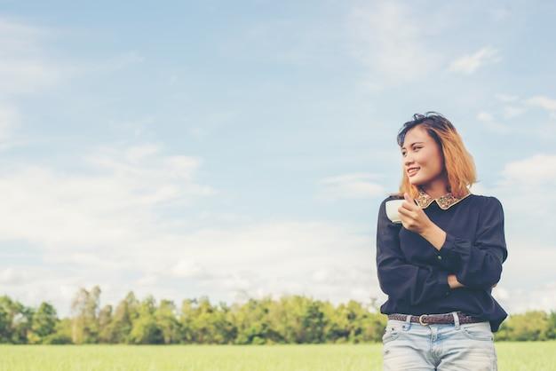 Ragazza sorridente con una tazza in un campo