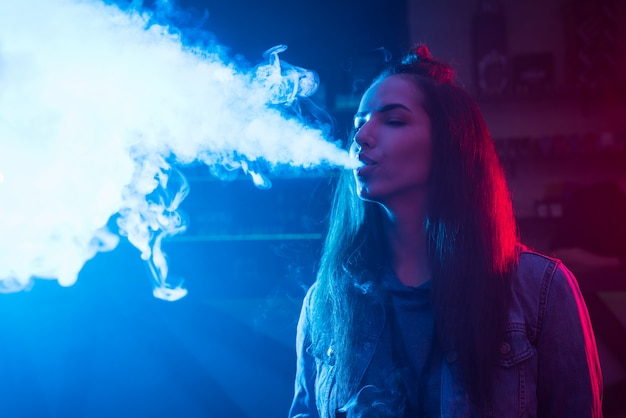 Girl smokes a cigarette and lets out smoke in a nightclub.