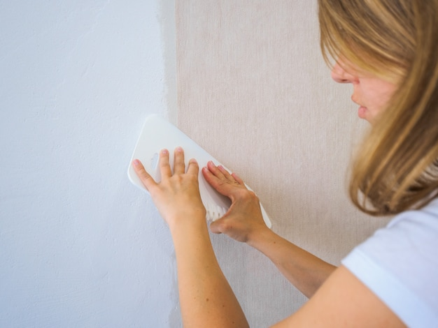 Girl smoothes the glued strip of wallpaper with a spatula