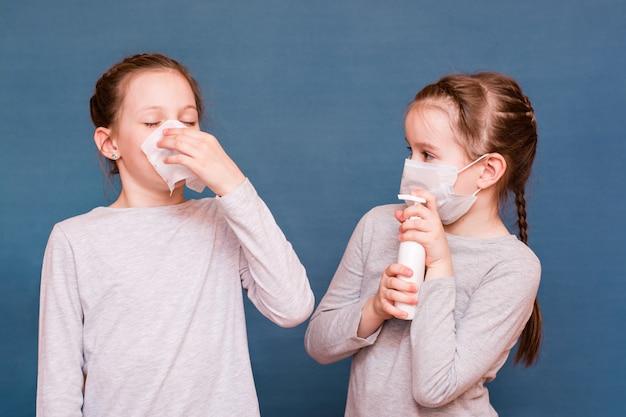 ハンカチの後ろに隠れているくしゃみをする女の子。 2番目の女の子は、マスクと消毒剤で保護されています。子供に感染する