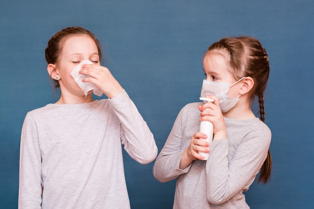 Girl sneezes hiding behind a handkerchief. the second girl is protected from her by a mask and a sanitizer. infecting children