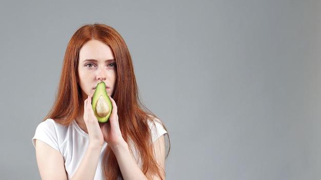 Девушка нюхает авокадо. молодая рыжеволосая девушка показывает авокадо на камеру