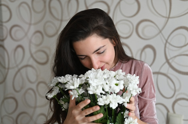 Девушка нюхает букет белых цветов. брюнетка обнимает нюхает букет нежных цветов от своей любимой. хороший подарок для любимой половинки.