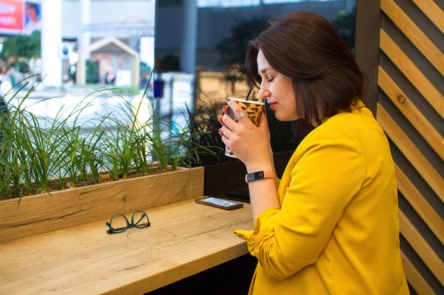 Girl sniffs a paper cup with leopard print and coffee with milk in the cafe.