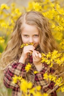 Девушка нюхает желтые цветы. ребенок на фоне форзиции. весенний портрет ребенка с цветами в волосах