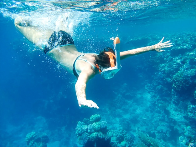 Girl snorkler swims underwater in the sea