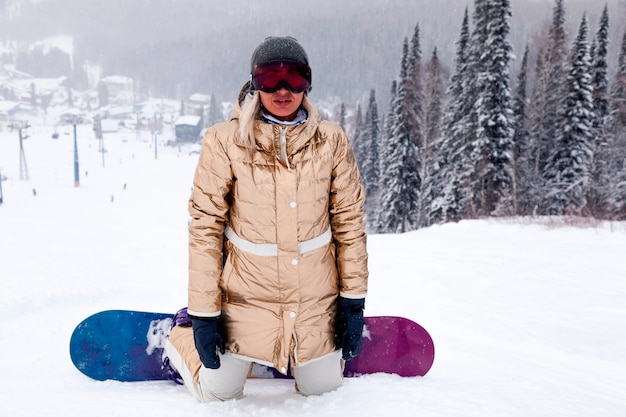 Girl snowboarder in golden sportswear and outfit in snowy high mountains forest. concept rest apres ski