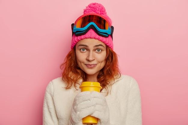 소녀 스노 보더는 따뜻한 겨울 복장, 흰색 장갑을 착용하고 분홍색 배경 위에 절연 테이크 아웃 커피를 보유하고 있습니다.