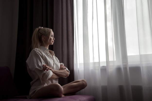 Girl on sofa at window of house waiting at sunlight from window. portrait of nice woman. home comfort and coziness. slavic female in morning in room. emotions and relax. concept of home relaxation