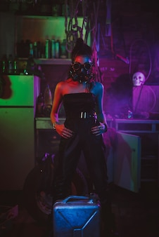 Girl soldier in cyberpunk style with a gas mask and glasses with neon lighting in the garage. steampunk style in a post-apocalyptic world