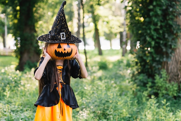Girl in sorceress clothes closing face by pumpkin