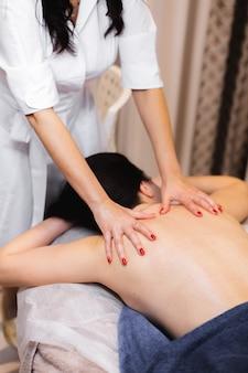 La ragazza nel salone spa riceve un massaggio alla schiena e al collo, giace sul lettino di cosmetologia, si rilassa e si gode il processo