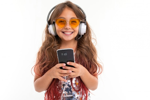 Girl in sparkling dress and yellow sunglasses, with big earphones listening to music and holding smartphone isolated
