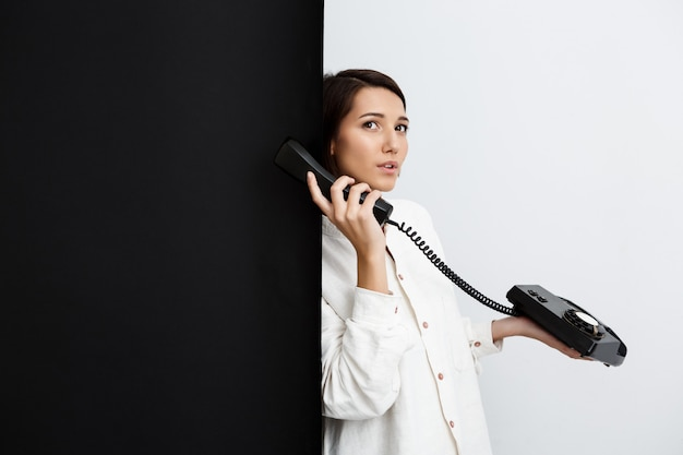 Girl speaking on old phone over black and white wall